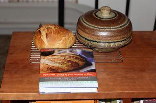 photo of bread cloche, bread baked in it and bread recipe book