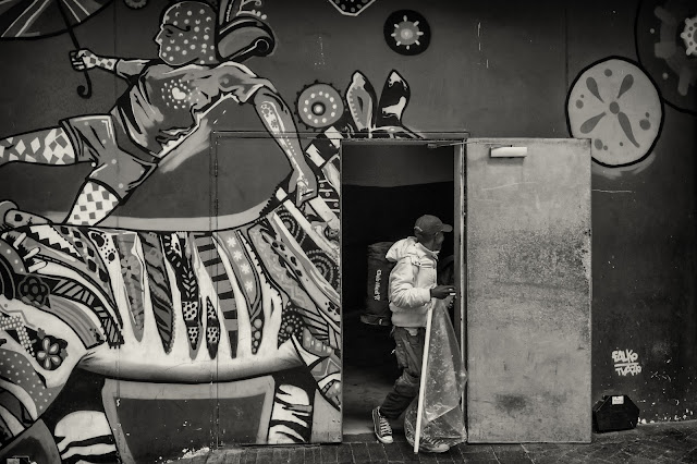 A man walks out of a door set in a wall with a mural of a zebra on it.