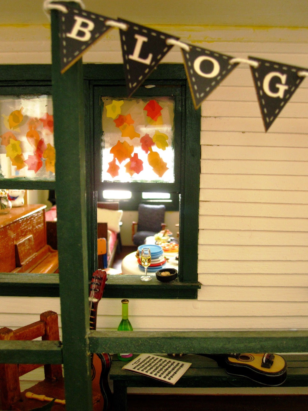 View of a miniature dolls' house veranda with a selection of musical instruments arranged on it. In front, tied to a paost, is bunting reading 'blog'.