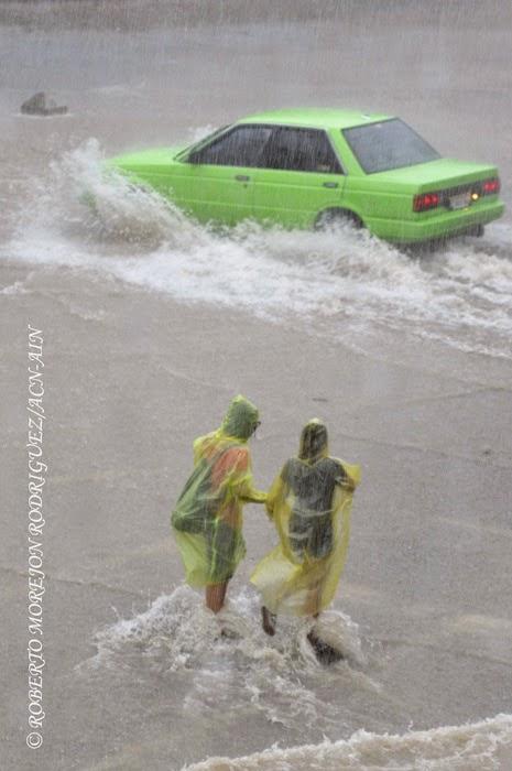 Dos personas caminan bajo la lluvia en la Calle 23 en el municipio Plaza de la Revolución, durante las lluvias caídas, en La Habana, Cuba,  el 29 de abril de 2015.