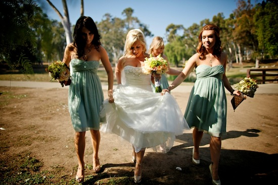 bride walking with her bridesmaids as they carry her dress