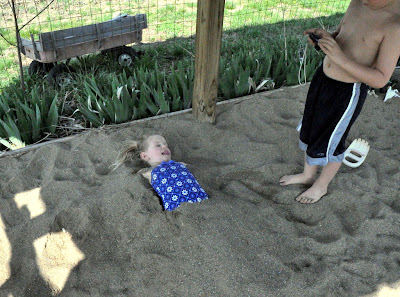 girl buried up to her waste in sand.
