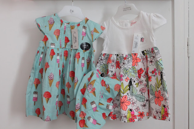 Two baby dresses one aqua with ice cream and lollipop pattern one white on top with bright flowers and leaves on the bottom