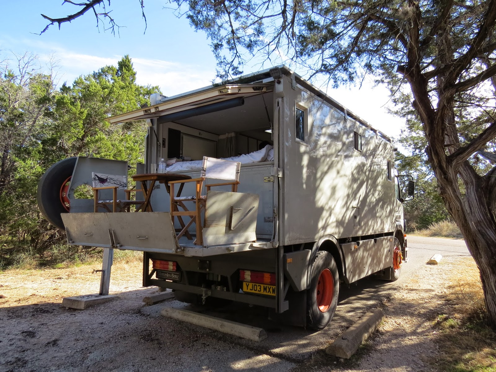 A mercedes 1823 overland motorhome with a dining table and chairs set up on the tail gate