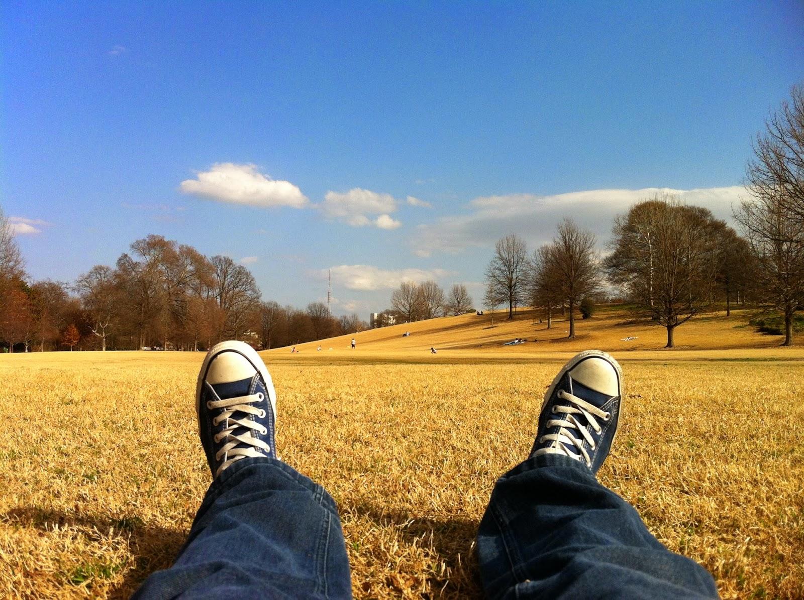 Zwei Beine mit Turnschuhen auf einem Feldboden liegend