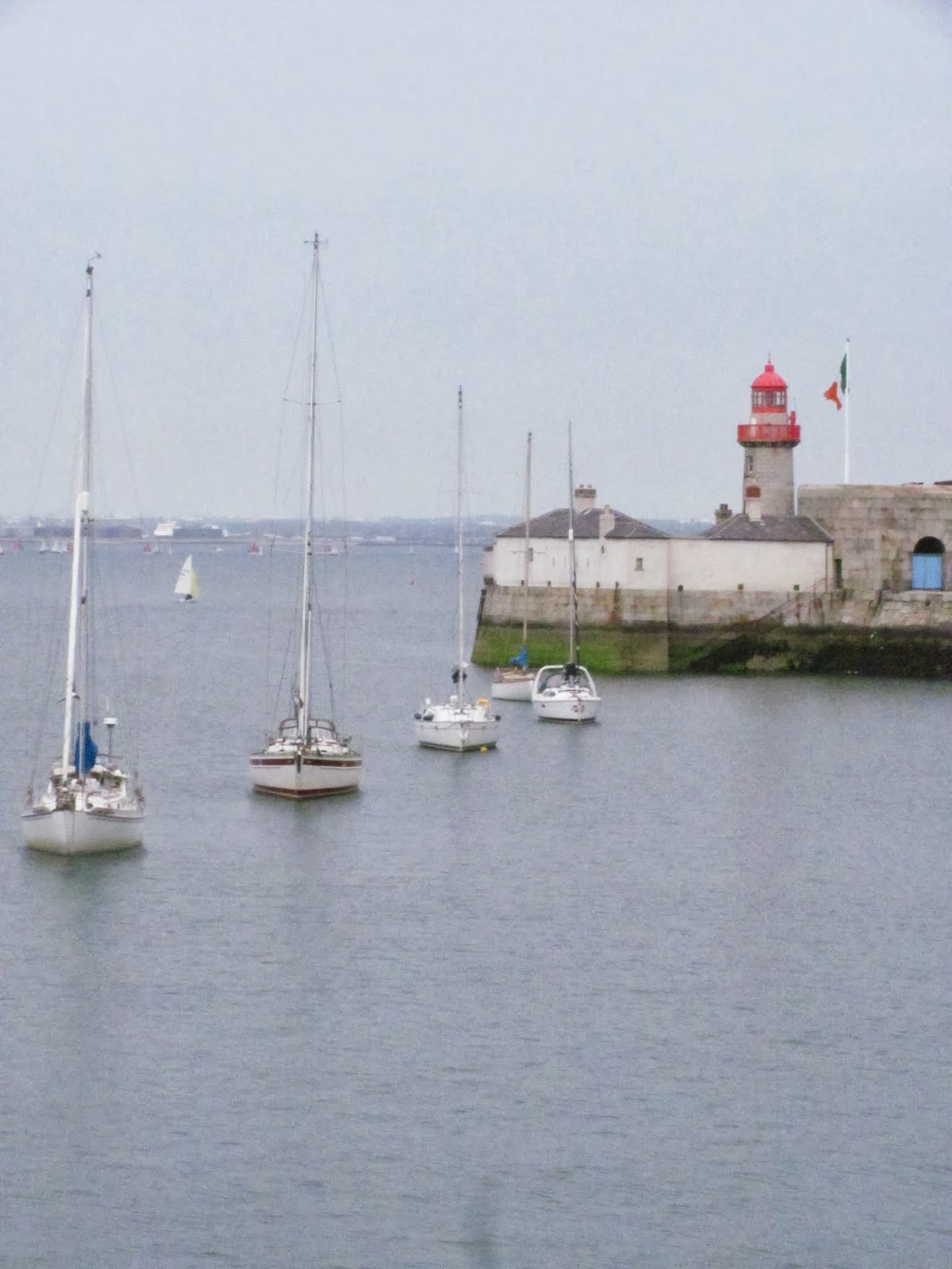 Sailboats exit the harbor past the red lighthouse at Dun Laoghaire, Co. Dublin, Ireland