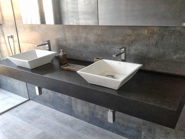 Encimera de granito negro anticato con dos lavabos de sobreencimera en porcelana blanca.