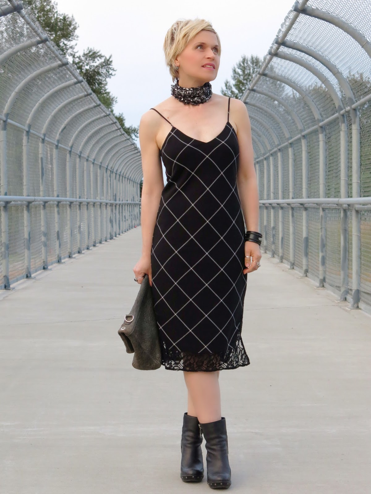 styling a black-and-white plaid slip dress with a scarf and chunky booties