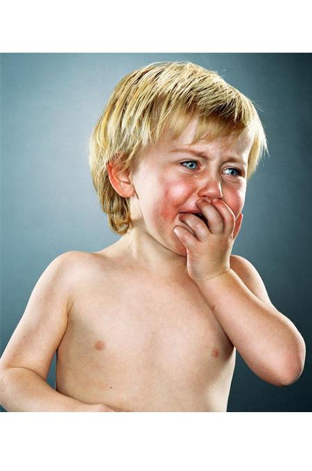 صورة طفل يبكي وهو يضع يده على فمه دون ملابس