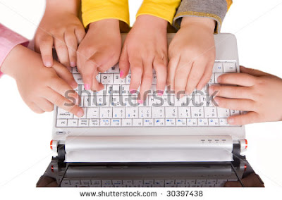 several children typing on one keyboard