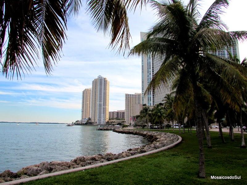 Foto do Bayfront Park mostrando a área gramada, coqueiros, o mar  e alguns prédios na Baía de Biscayne