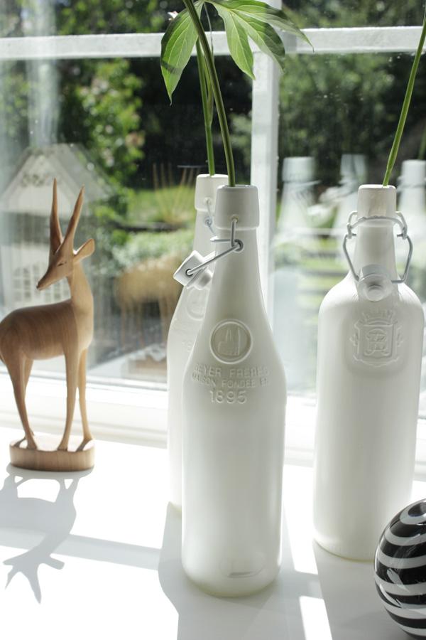 svart och vit randig porslinsboll, vit spray på flaskor i fönstret, vita flaskor med blommor från trädgården, diy vaser, afrikansk hjort