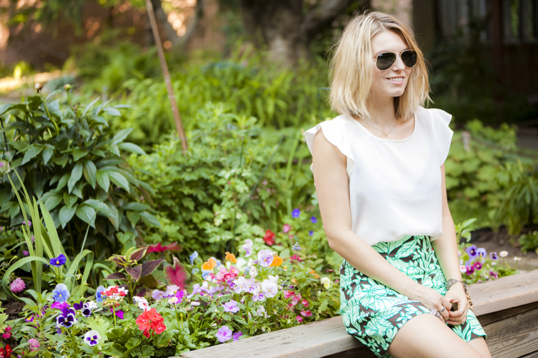 Joe Fresh white silk frilly blouse, Zara tropical print shorts, Ray-Ban green/gold aviators, in the garden by the flowers, messy blond bob