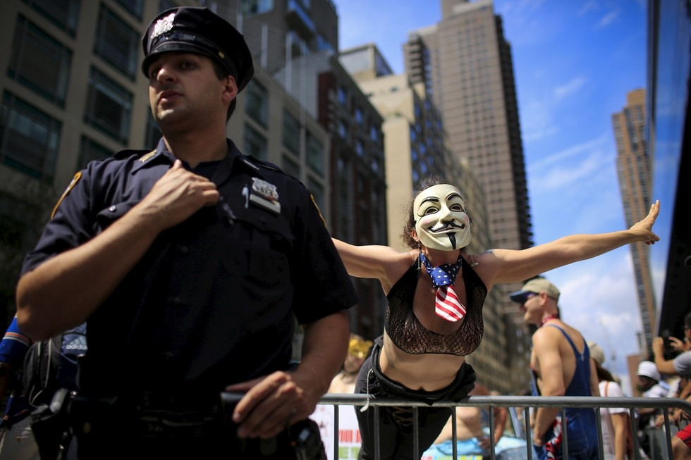70 Of The Most Touching Photos Taken In 2015 - A woman poses next to a New York Police Officer as she awaits the start of a topless march in New York City.