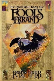 cover art for Fool's Errand, featuring two pale skinned men, one of whom has long white hair, riding black and white horses down a hill with a wolf beside them
