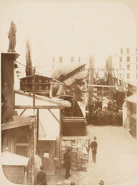 [View of the external area of the workshop in Paris, showing construction materials, the head of the Statue of Liberty, and a group of men gathered in front of the left foot of the statue.]. Fernique, Albert -- Photographer. 1883. Source: Album de la construction de la Statue de la Liberte. Repository: The New York Public Library. Photography Collection, Miriam and Ira D. Wallach Division of Art, Prints and Photographs.