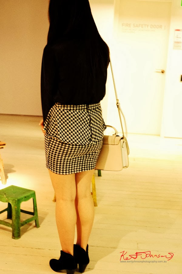 Black blouse hounds-tooth check skirt with black ankle boots; at Serve the People art opening at White Rabbit Gallery.