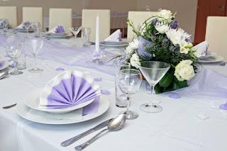 Mesa puesta con vajilla, cristalería, cubertería, textil de mesa y arreglos florales