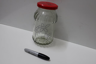 drawing a design on jar using marker