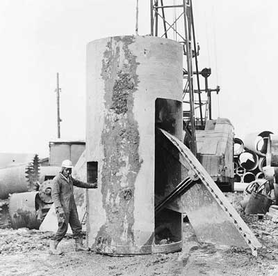 The bell is formed at the bottom of the  caisson shaft by a belling bucket with retractable cutters. The example shown  here is for an 8-foot- (2.44-m)-diameter shaft and makes a bell 21 feet (6.40 m) in  diameter.