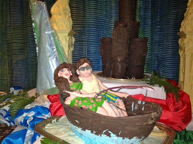 dessert buffet sculpture of people in a boat with a castle in the background