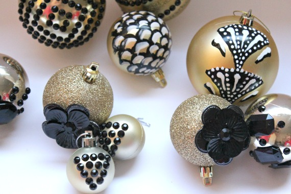 photo of diy hand decorated Christmas baubles with black and gold glitter and gemstones