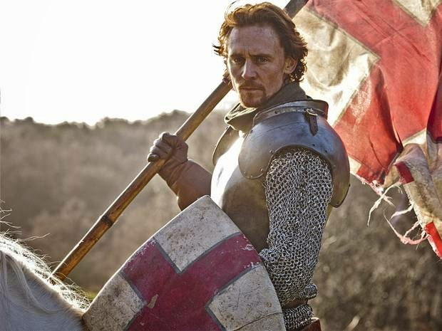 Tom Hiddleston on a horse carrying the flag of England.
