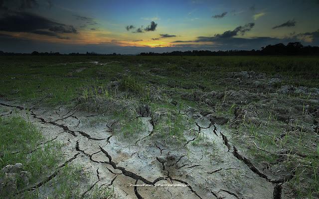 Gambar sunset kering dengan tanah merekah