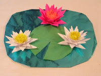 Each Centerpiece Had Three Lillies One Lilly Pad And Puddle The Blue Foil Of Simulates Water By Providibg