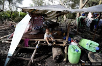 A child sits amongst the remains of a house destroyed by Typhoon Rammasun in a coastal village of sea gypsies, also known as Badjaos, in Batangas city, south of Manila, July 17, 2014.  (Credit: Reuters/Erik De Castro) Click to Enlarge.