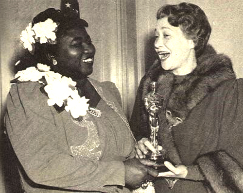 "Hattie McDaniels (left) was the first African-American to win an Oscar for her role in Gone With The Wind.  In the film her character was actually named ""Mammy"". It would be 51 years before another African-American  woman would win an award (Whoopi Goldberg in Ghost, where she played a maid-like facilitator, similar to  McDaniel's ""Mammy"" character)."