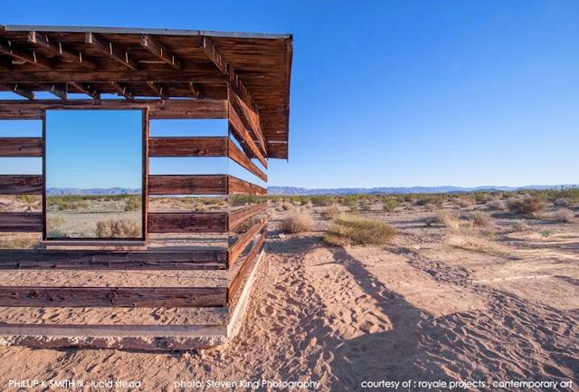 Cabaña transparente de madera y espejos en un paisaje desértico
