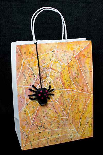 Spider web Trick or treat bag made using a white crayon as a watercolor resist with cute black spider with pink spots