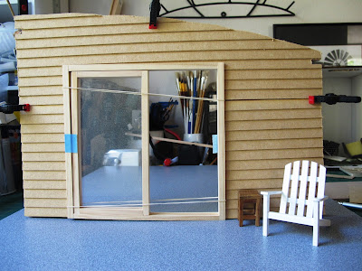 Wall of a dolls' house kit, with weatherboarding clamped to it,  and a sliding door dry fitted. The wall is standing on a piece of board that looks like concrete, and a dolls' house miniature Adirondack chair is in front of it.