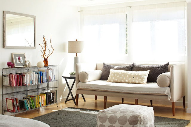 Cozy modern den with wire bookshelf, neutral sofa, ottoman and wood floors