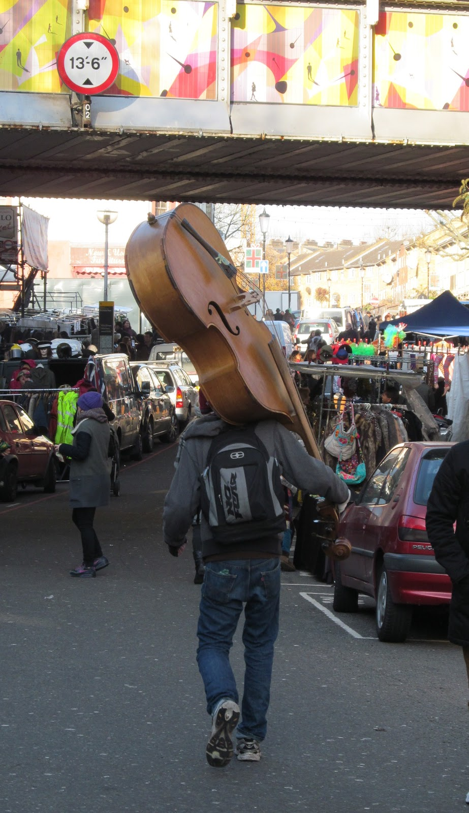 man carrying a double bass on his shoulder