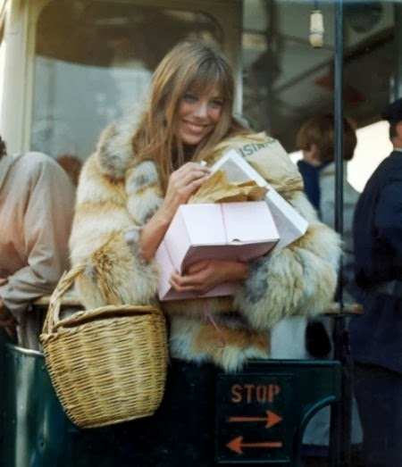 Jane Birkin with her iconic straw basket wearing a fur coat and carrying boxes