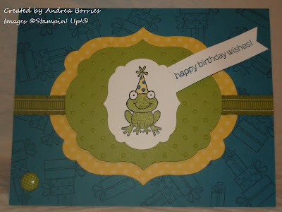 "Dark blue card with presents stamped on the background. The focal image is a layer of yellow polka dot paper, a layer of polka dot embossed green card stock and a white layer stamped with a from wearing a birthday hat. A banner is stamped with ""happy birthday wishes."""