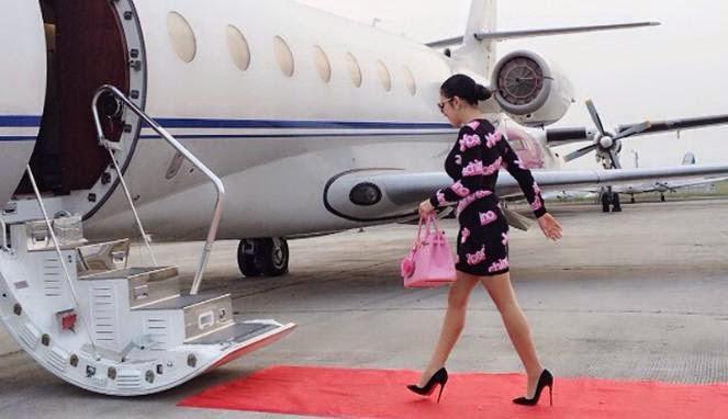Syahrini saat berjalan menuju pesawat pribadi