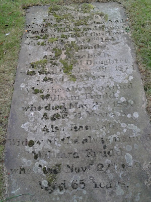 A laid down flat, moss covered gravestone, transcription in the text adjacent.