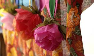 rosas de papel crepon decorando a parede com chita