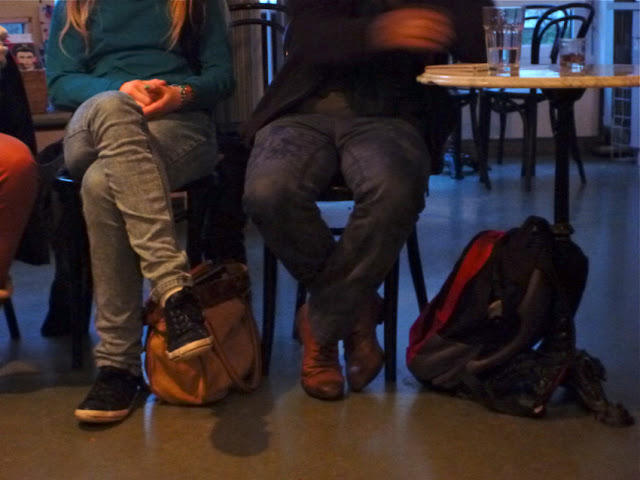 Hinten die Dämmerung, im Vordergrund sitzende Menschen, Rucksäcke, ein Tisch