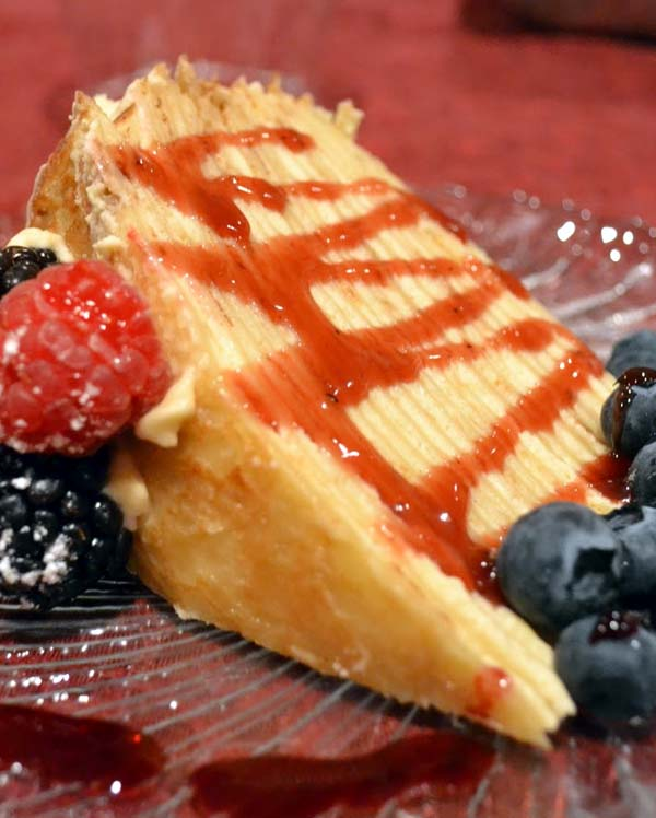 Easy Crepe Cake Recipe with Orange Raspberry Sauce. Making one takes awhile, but it's worth it.