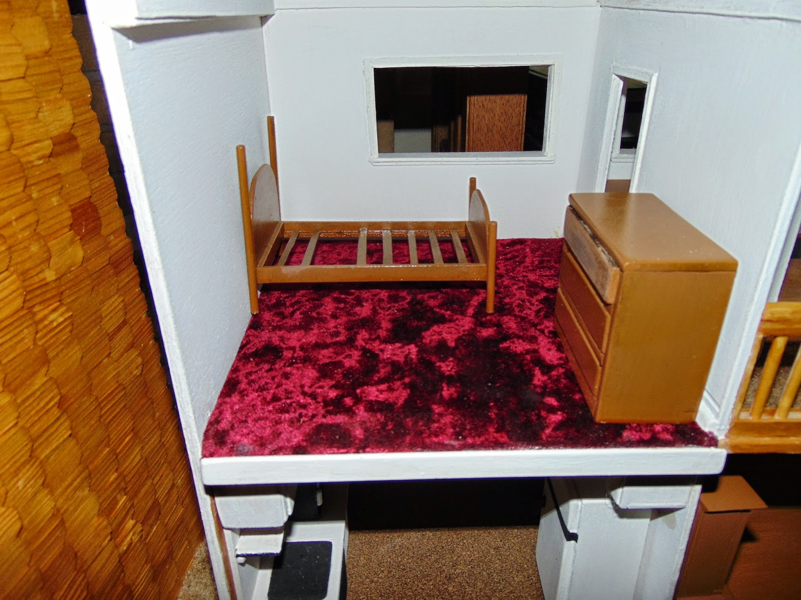 Bed with no mattress or bedspread in dollhouse bedroom