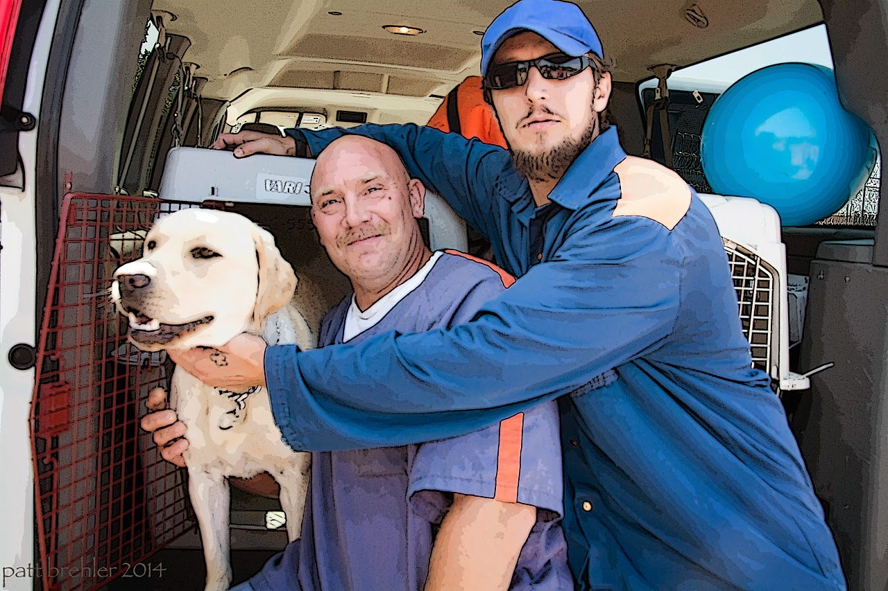 Two men wearing blue prison shirts (the man on the right is also wearing a blue ball cap) are facing the camera with a yellow lab dog to the left. The dog is coming out of the airline crate that is in the back of a van. The man in the middle has his right arm wrapped around the dog's back and is smiling at the camera. The man on the right with the ball cap is reaching his right arm over the other man along the top of the crate and his reaching his left arm in front of the other man to pet the dog under his chin. The man with the ball cap is wearing sunglasses and has a serious look on his face.