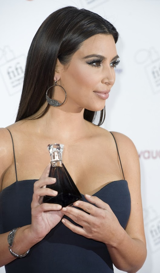 KIM KARDASHIAN posing for photographers with  The FiFi  Fragrance Awards in her hand