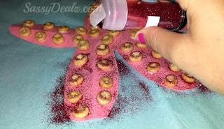 putting pink glitter on the cheerios starfish