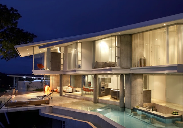 Photo of incredible modern home at night with the swimming pool and terrace
