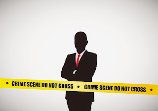 Man in suit stand behind crime scene tape.