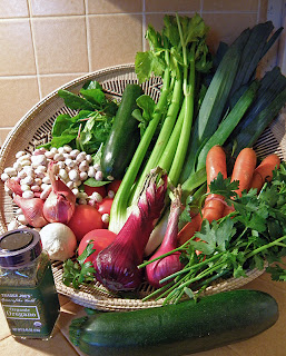 Basket of celery, carrots, onion, garlic, beans, zucchini, herbs, parsley, spinach